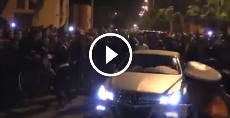 صورة الملك وسط حشود جماهيرية بأحد الأحياء بالعيون